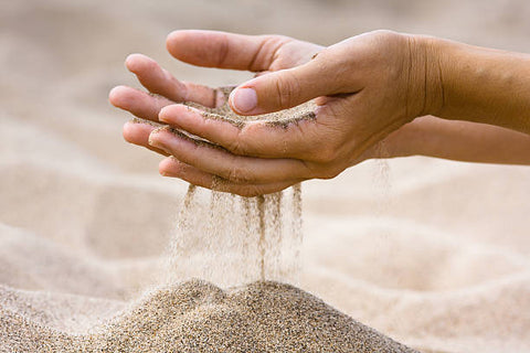 Hands touching sand