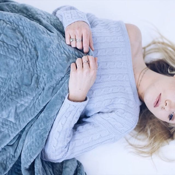 woman lying down and holding a gray weighted blanket