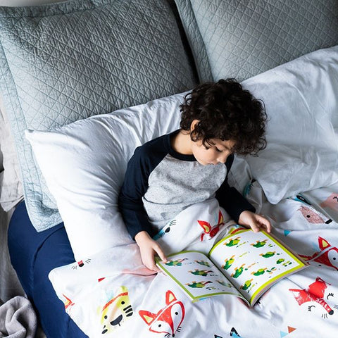 little boy reading a book under Hush weighted blanket for sensory issues