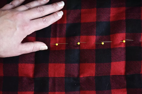 Person sewing the checks fabric to create pockets