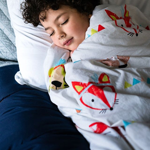 little boy sleeping peacefully wrapped in Hush weighted blanket for sensory issues