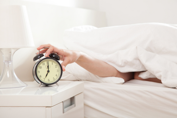 Person in bed, under a blanket, switching off the alarm clock