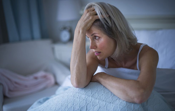 Woman sitting in bed and looking a bit stressed