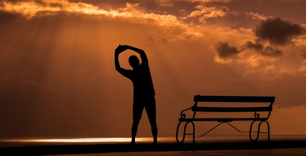 Person stretching at sunset