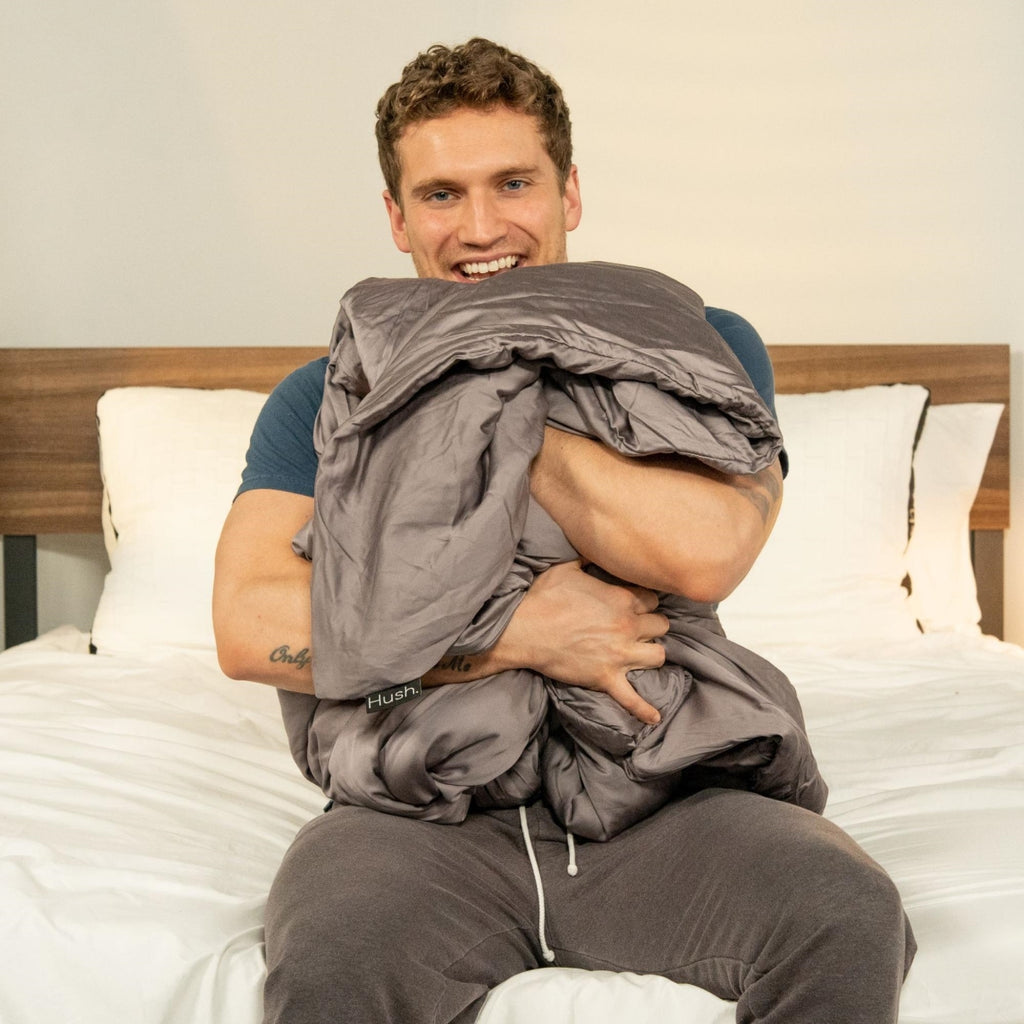 do weighted blankets work: Smiling man hugging a weighted blanket while sitting at the foot of his bed