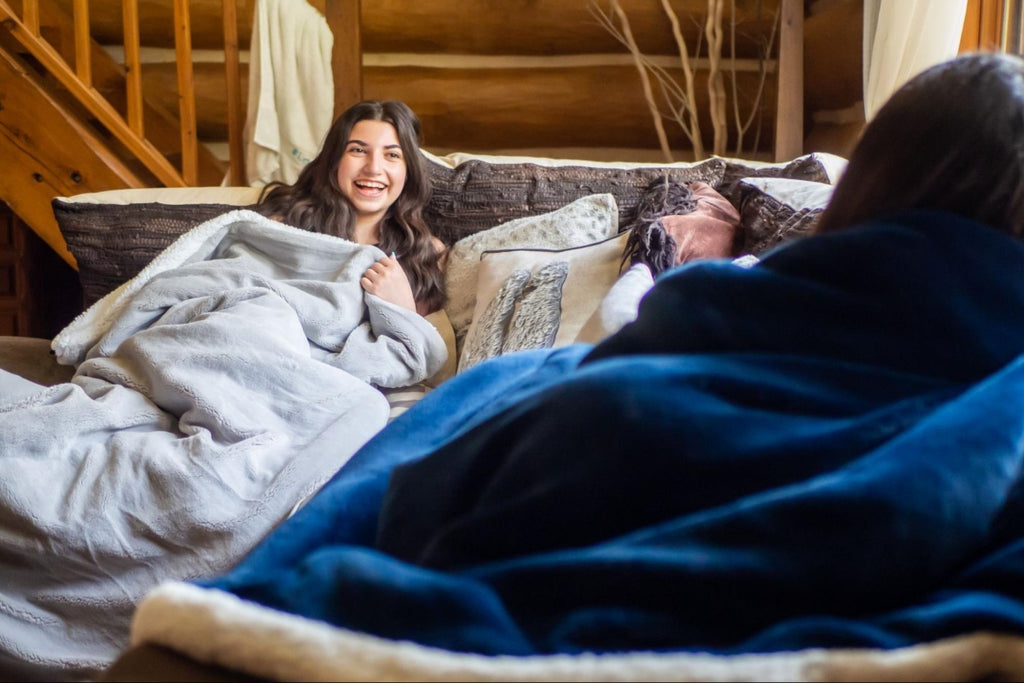 gifts for people with anxiety: Two girls chatting while sitting on a couch with blankets