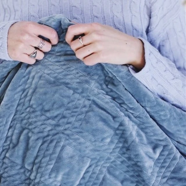 do weighted blankets work: Woman's hands holding the edge of a blanket