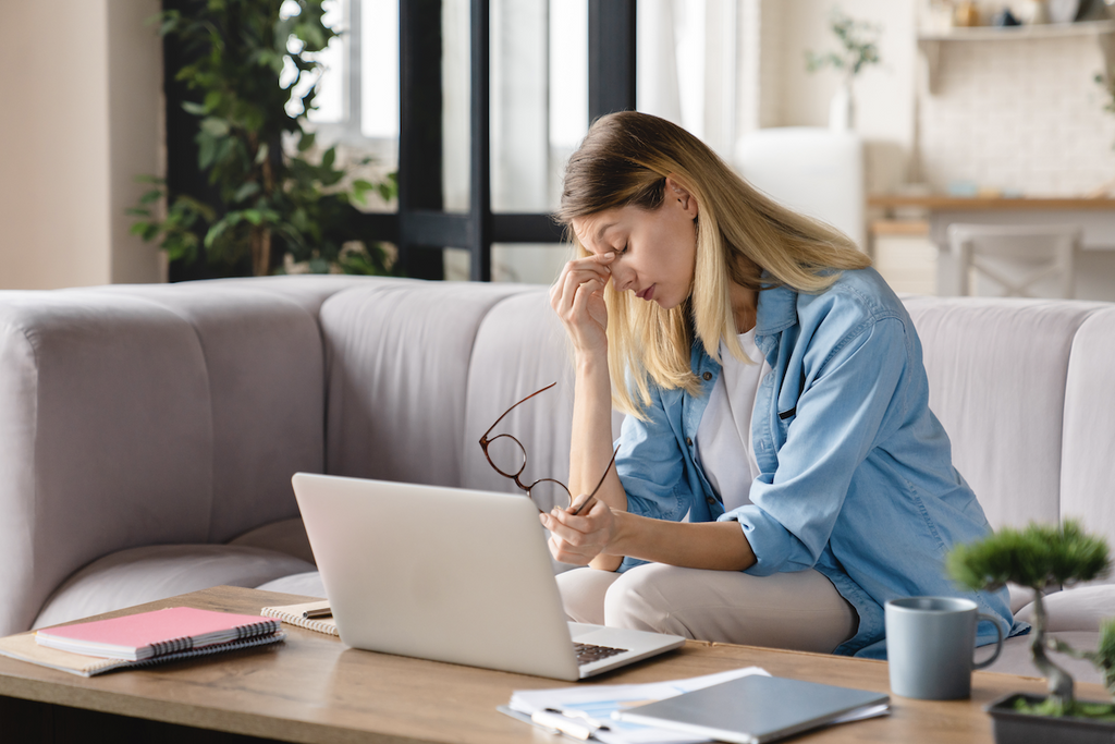 poor sleep hygiene: Tired woman rubbing the bridge of her nose while sitting in front of her laptop
