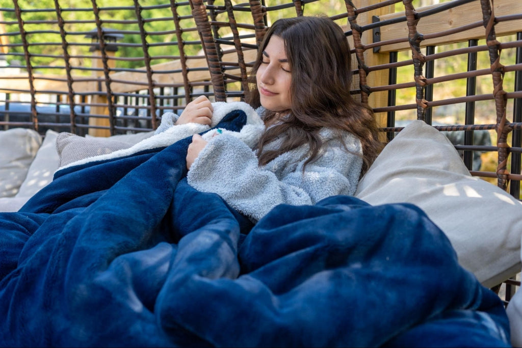 Woman with a blanket with her eyes closed while sitting outdoors