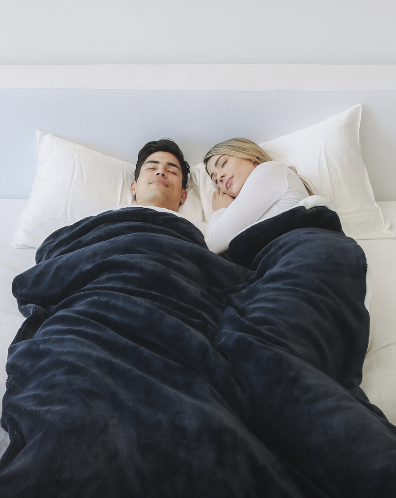 Couple sleeping in bed with a blanket