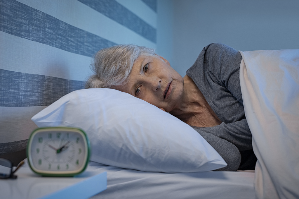 can you catch up on sleep: Elderly woman having trouble sleeping and staring at her alarm clock