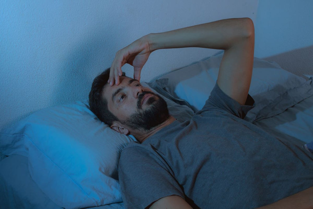 How long does it take to fall asleep: Man lying awake at night