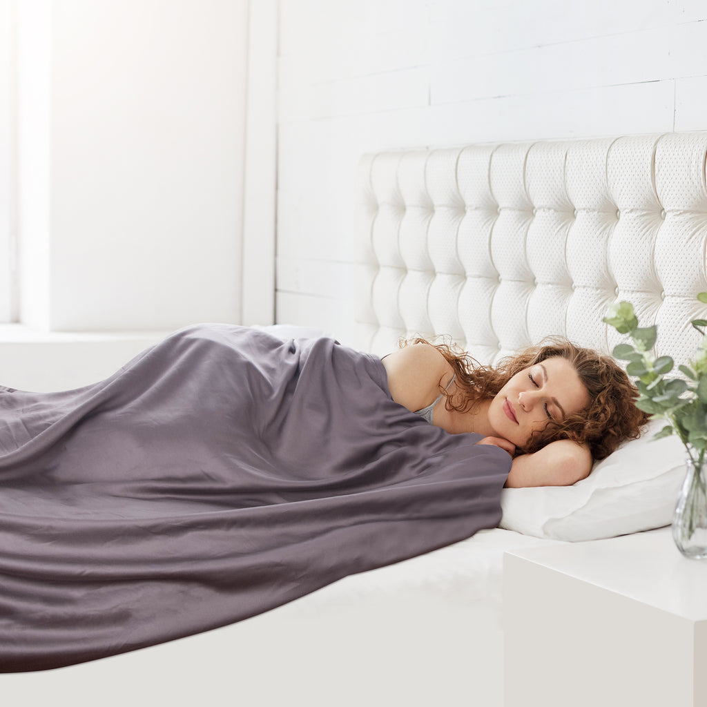 are weighted blankets safe: Woman sleeping in bed with a blanket