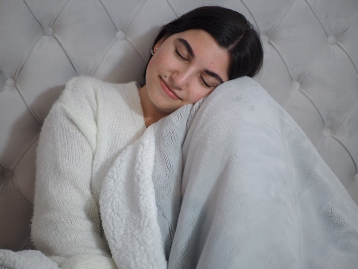 night routine: Woman hugging a blanket with her eyes closed