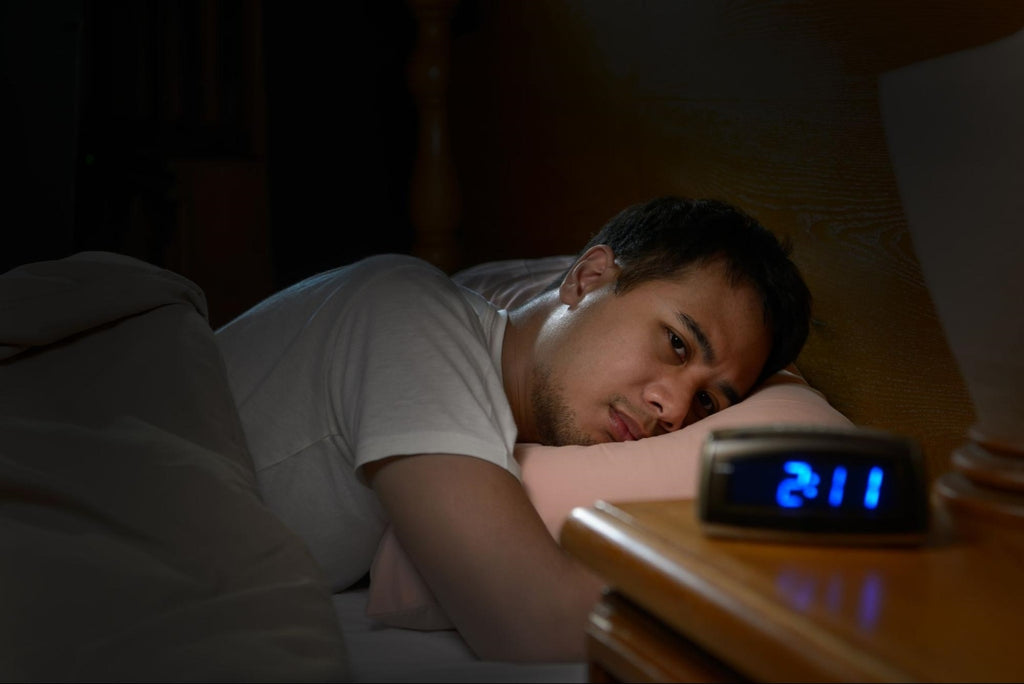 how to stay asleep: Man having trouble sleeping and staring at his alarm clock