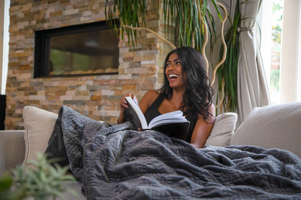 how to make yourself tired: Woman laughing while sitting on a couch with a blanket and holding a book
