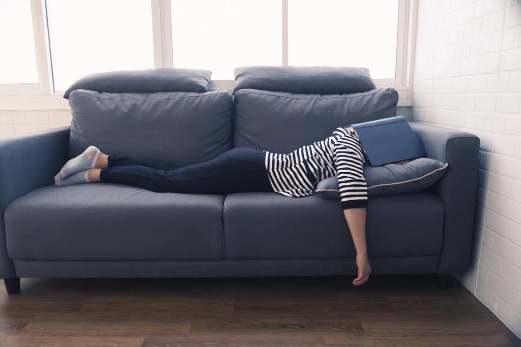 sleep latency: Woman lying face down on a couch with a book covering her head