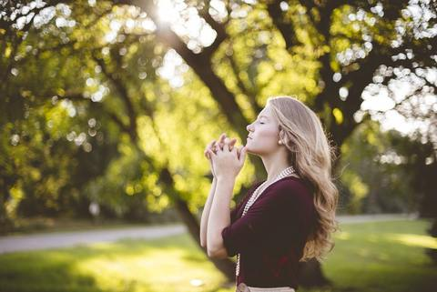 Woman in a meditation pose outdoors with her eyes closed