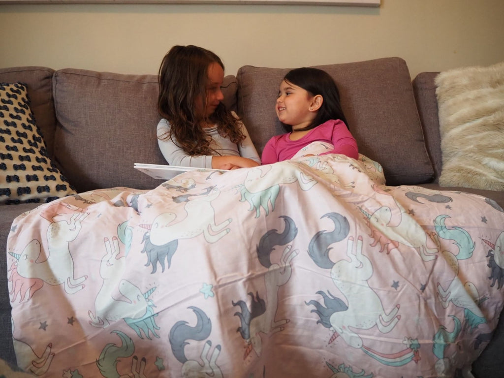 Two little girls talking while sitting on a couch with a blanket over their legs