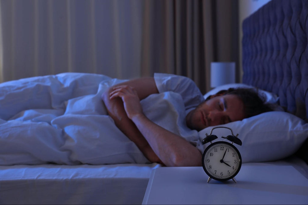 how to stay asleep: Man sleeping with an alarm clock on his nightstand