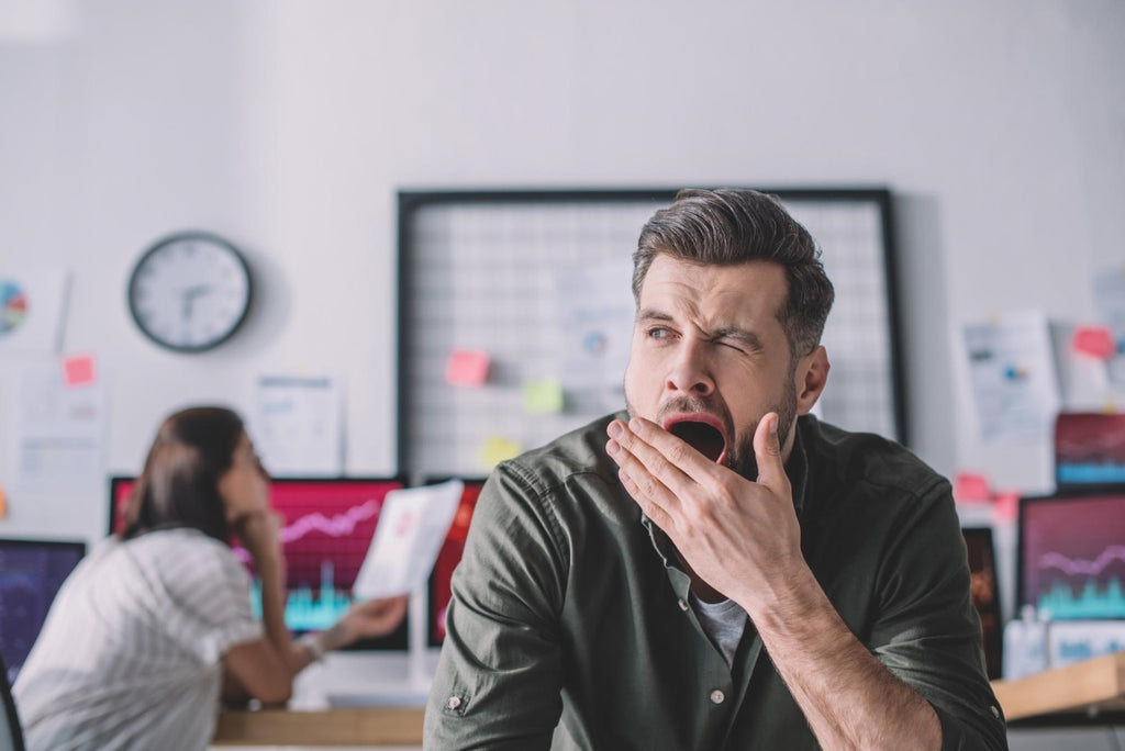 sleep latency: Man yawning while at the office