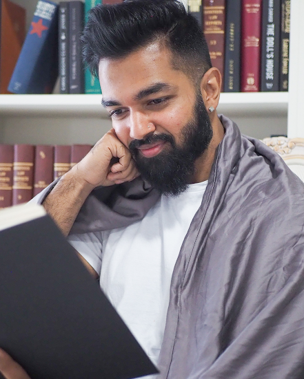 how to use a weighted blanket: man reading with a blanket over his shoulders