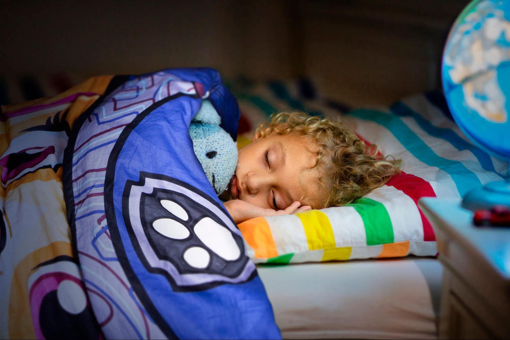 are weighted blankets safe: Young girl sleeping in bed with a blanket and stuffed toy