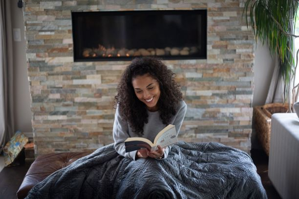 Woman sitting on a couch with a blanket while reading a book