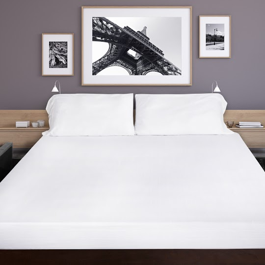 cooling bed sheets: Photo of a bed with white sheets and framed black and white pictures on the wall