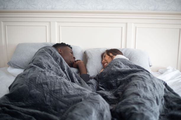 Couple lying in bed while looking at each other with a blanket