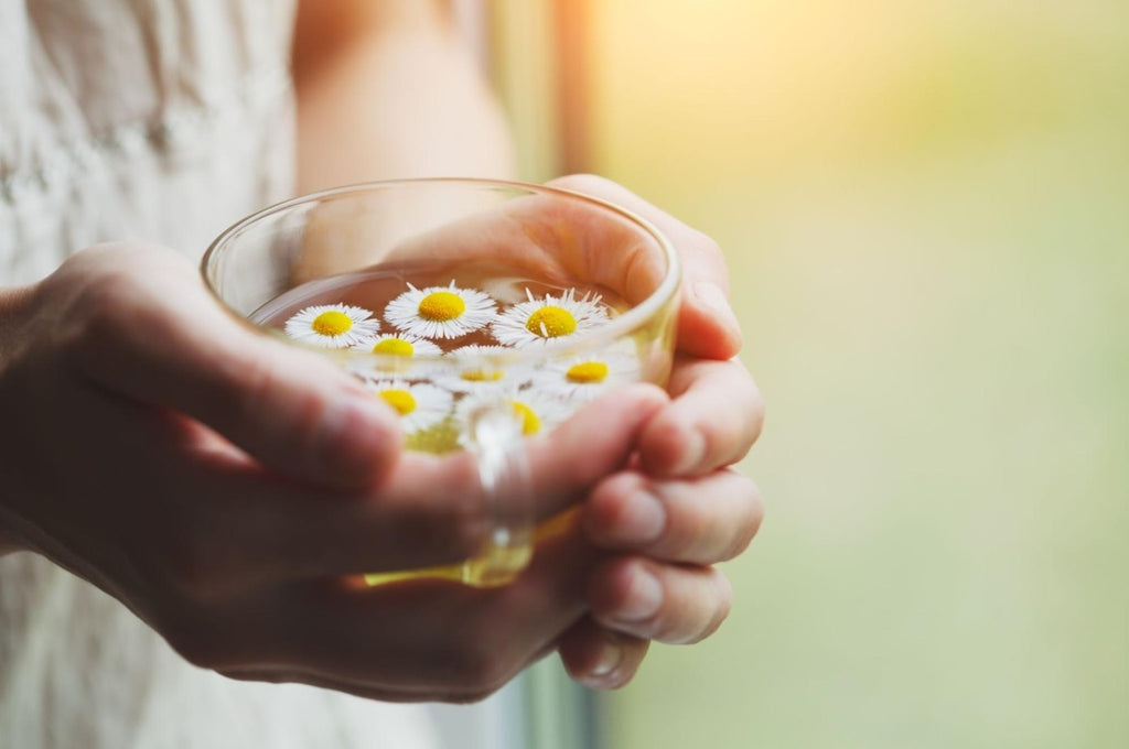 Woman holding a cup of tea with chamomile flowers