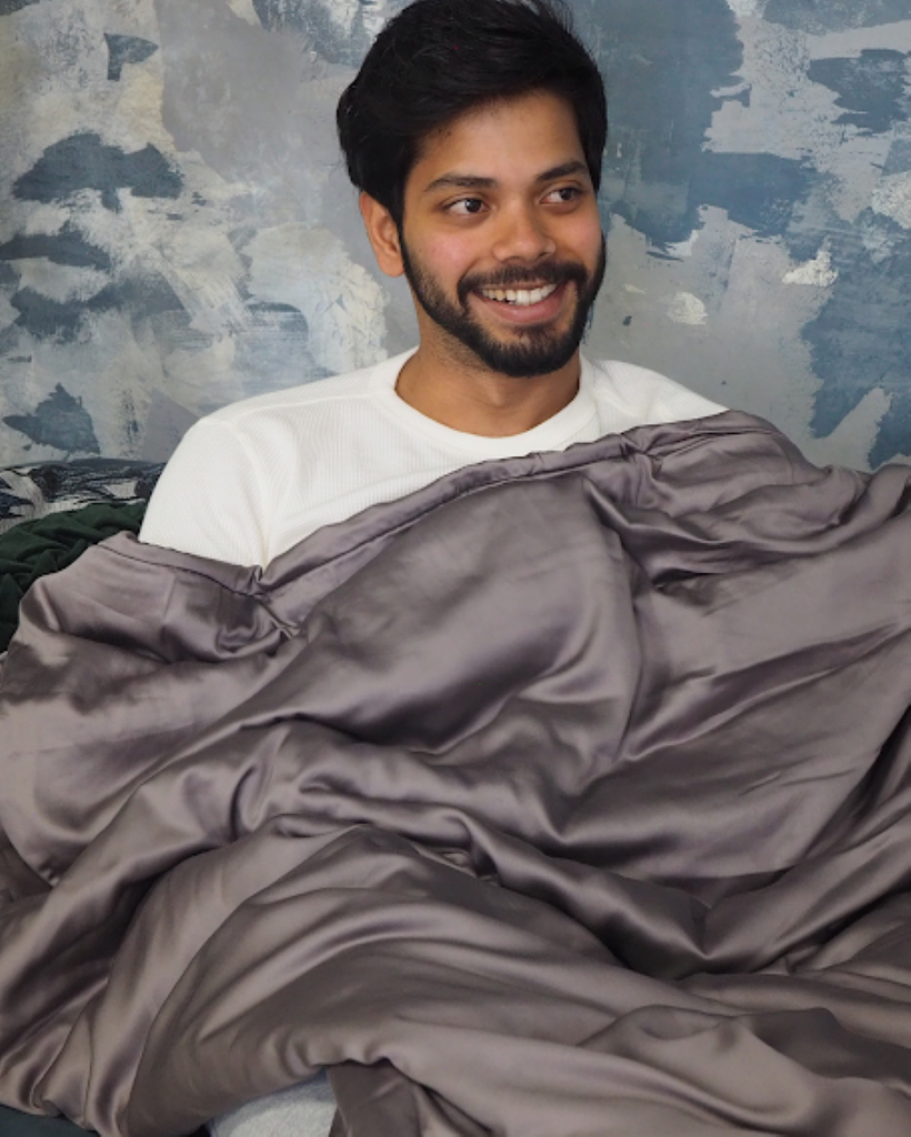 Smiling man leaning against a wall while covered in a blanket