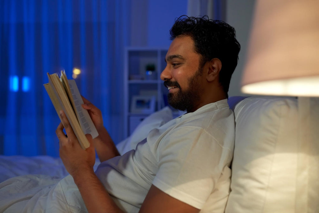 sleep latency: Man smiling while reading a book in bed