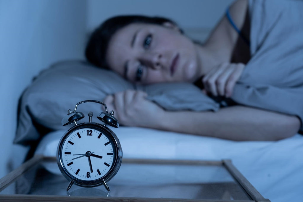 nighttime anxiety: Woman lying in bed while staring at her alarm clock