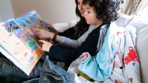 weighted blankets for kids: Child listening as his mother reads a bedtime story