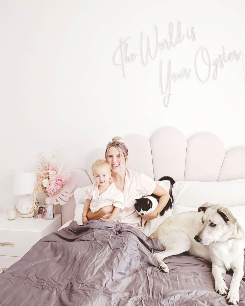 Smiling woman sitting in bed while holding her baby, cat and dog with a blanket