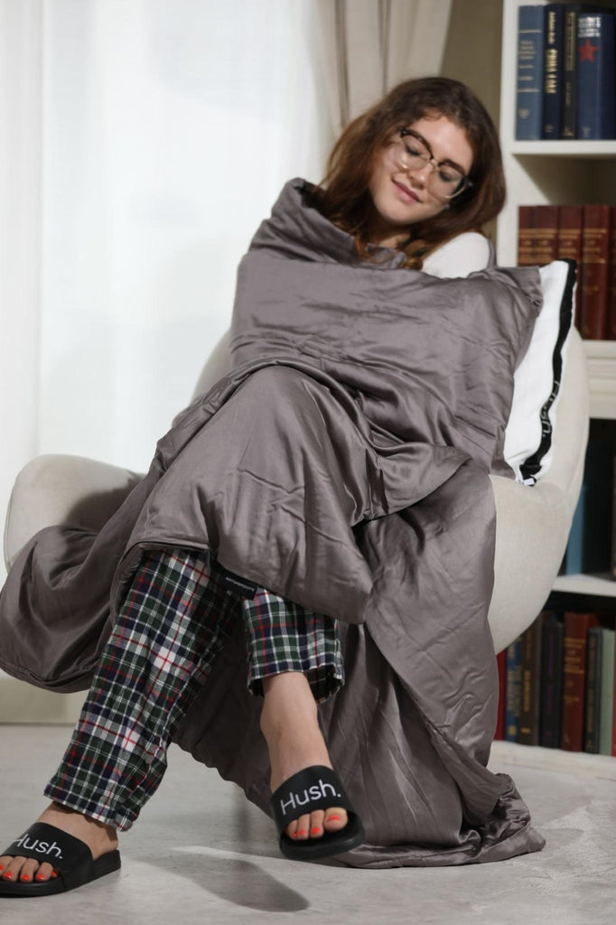 Smiling woman with a blanket wrapped around her