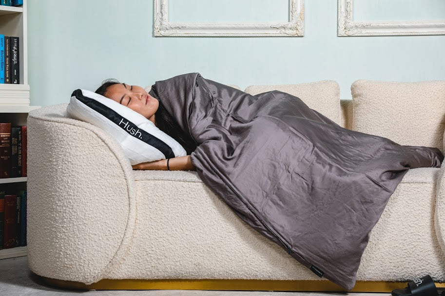 Woman sleeping on a couch with a pillow and blanket