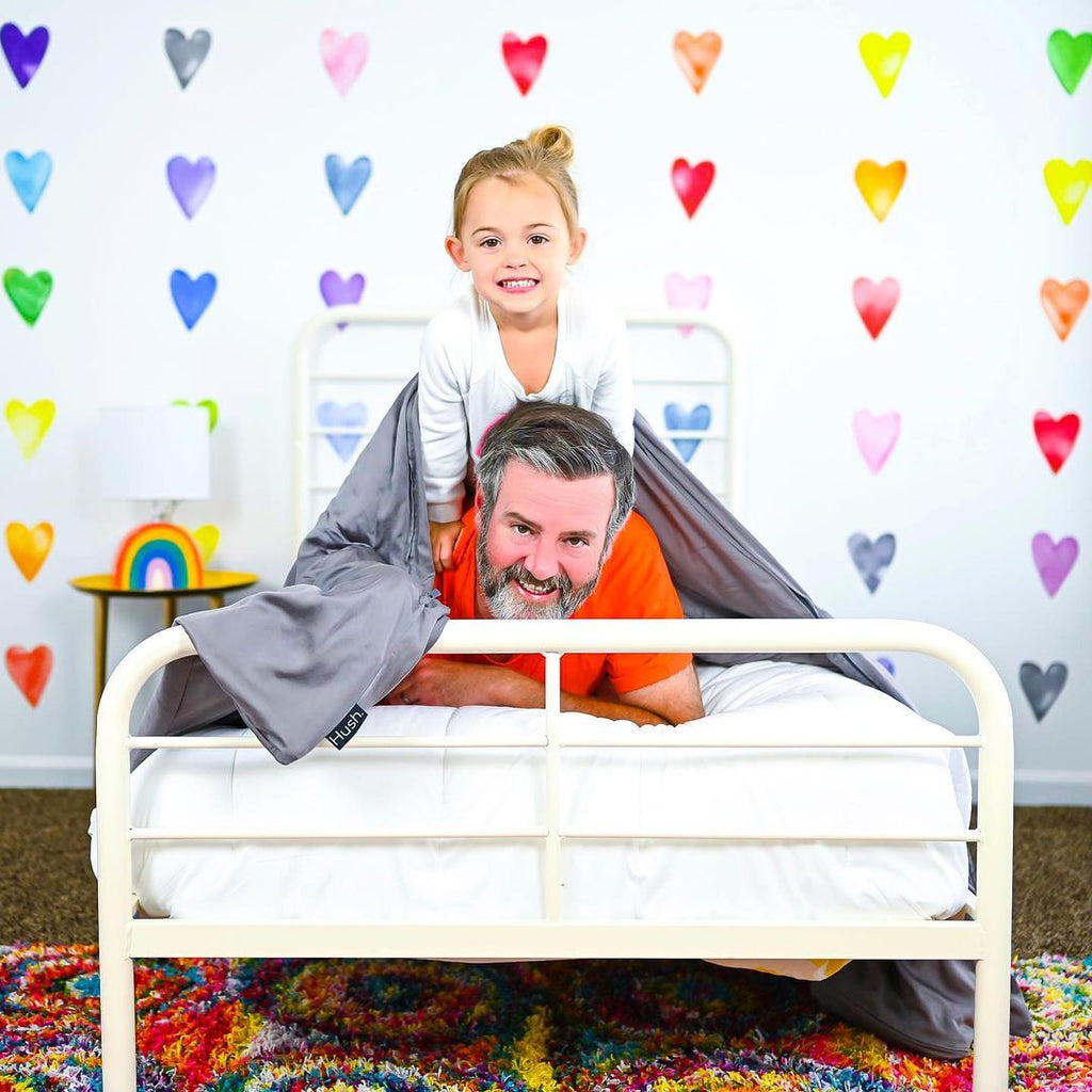 are weighted blankets safe: Father and daughter looking at the camera while in bed with a blanket
