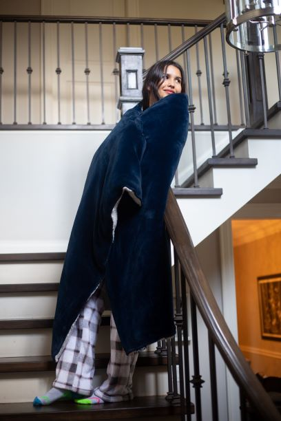 Woman standing on the stairs with a blanket wrapped around her