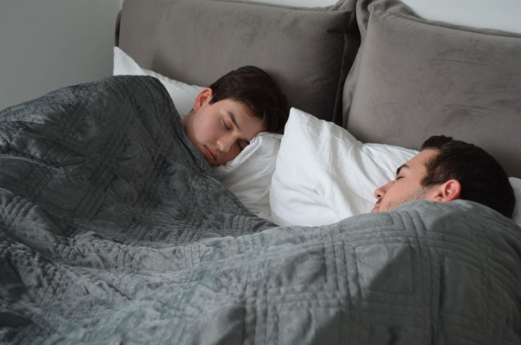 Couple sleeping in bed while covered by a blanket