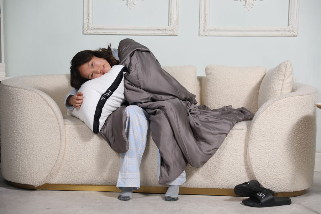 are weighted blankets hot: Woman sitting on a couch while hugging a pillow with a blanket