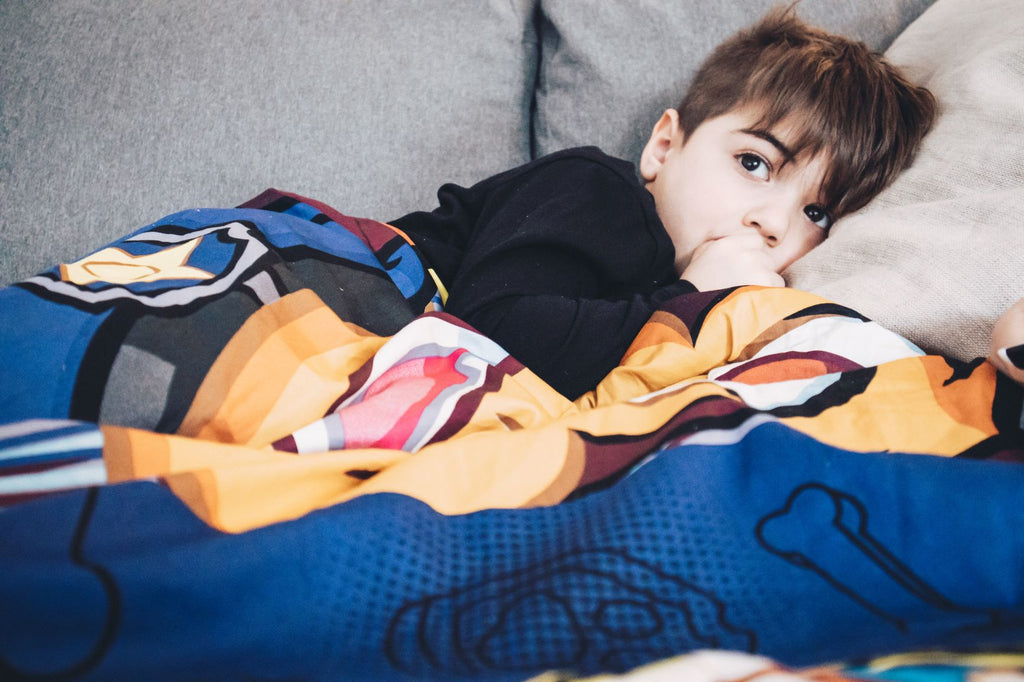 Young boy lying in bed with a colorful blanket