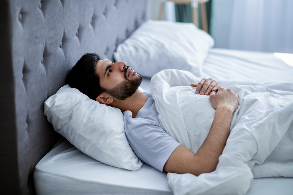waking up with anxiety: Man lying in bed while staring at the ceiling
