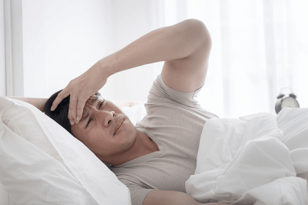 waking up tired: Man massaging his forehead while lying in bed