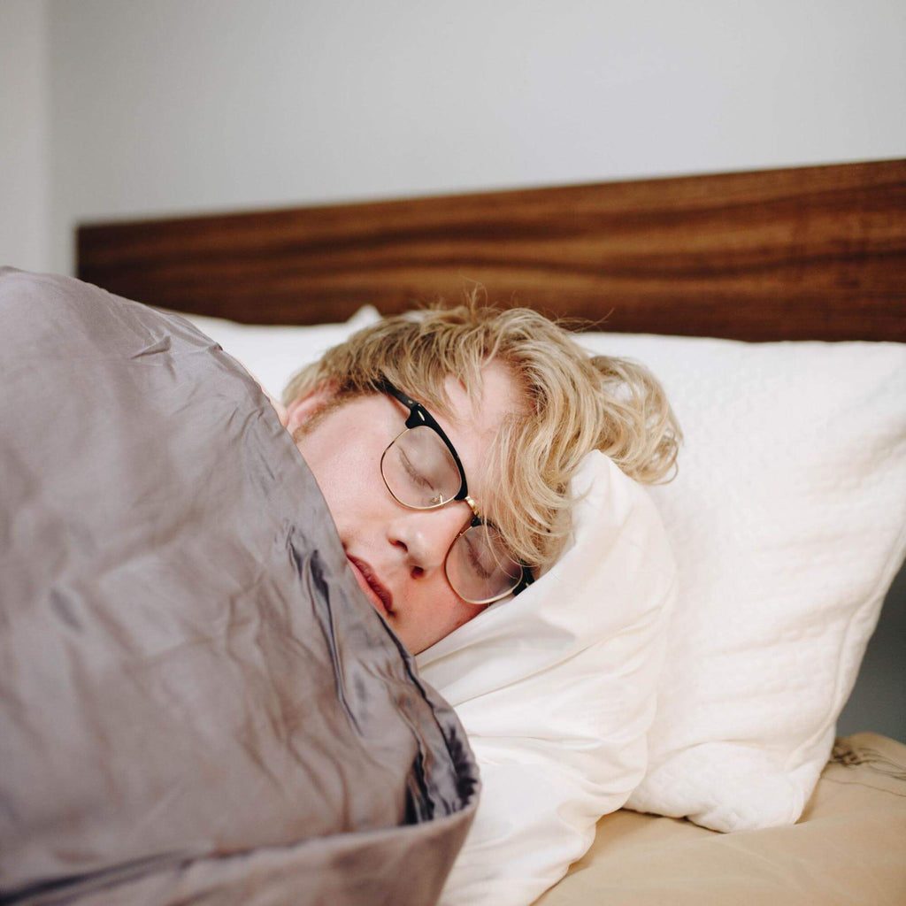 waking up tired: Man sleeping with a weighted blanket while wearing his eyeglasses