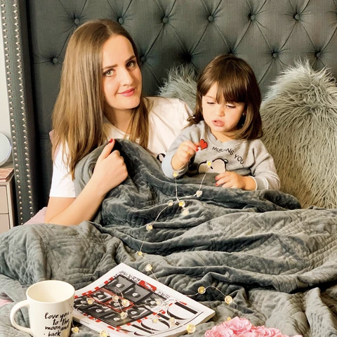 weighted blanket for ADHD: Mother and daughter sitting in bed with a blanket, coffee mug and a magazine