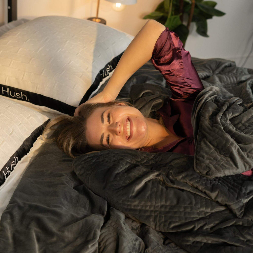 Smiling woman lying in bed with Hush pillows and weighted blanket
