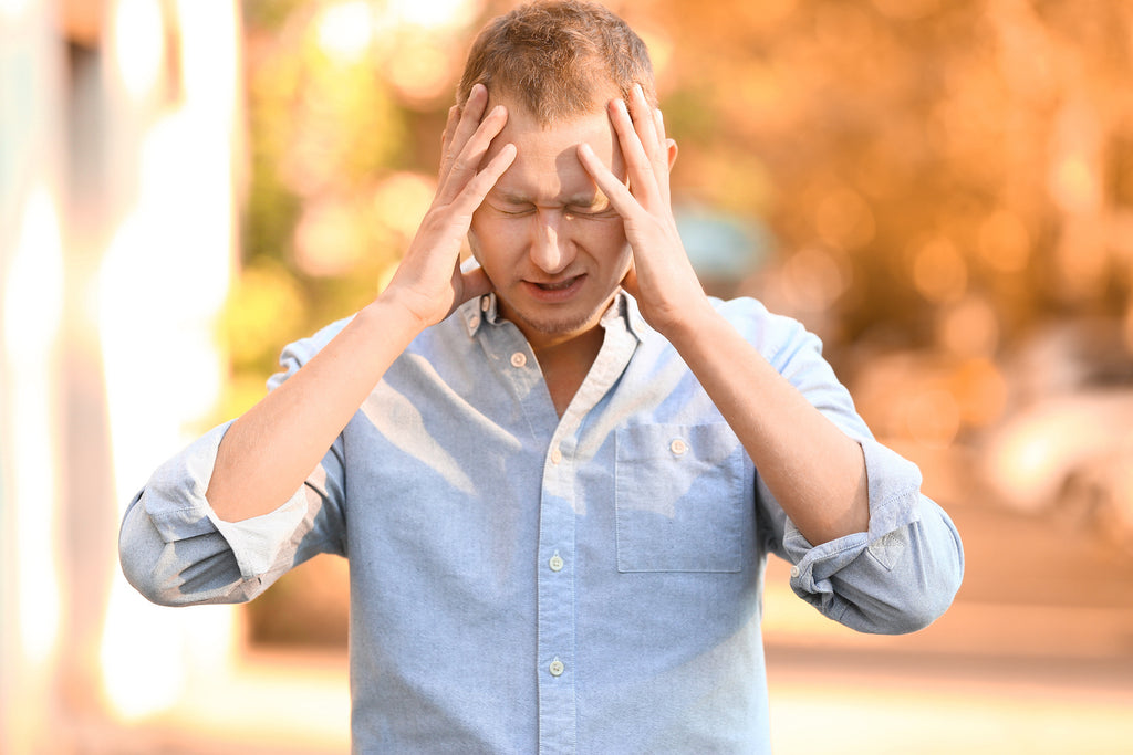 sensory overload anxiety: stressed man holding his head