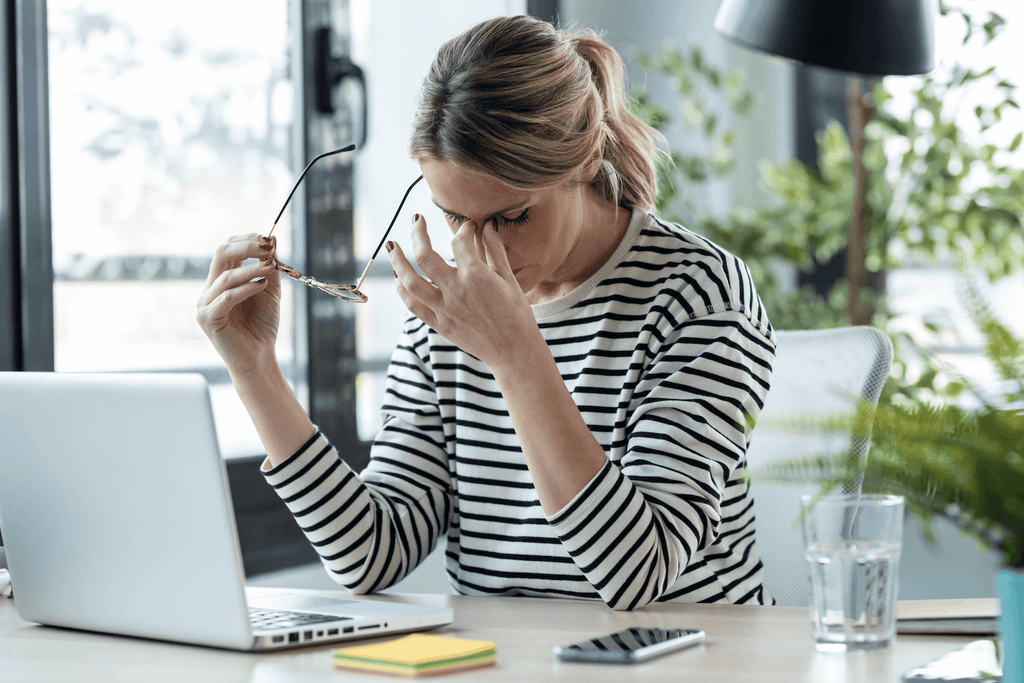 types of stress: stressed woman pinching the bridge of her nose